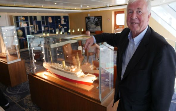 Torstein Hagen standing next to a ship model