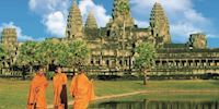 Three monks standing in front of Angkor Wat
