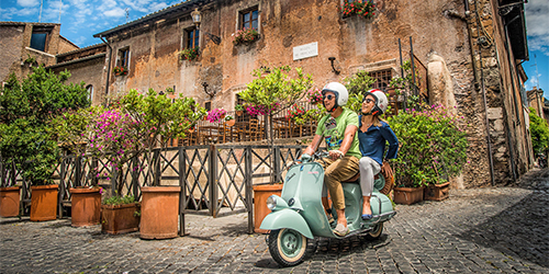 Two people riding on a vespa in Rome, Italy
