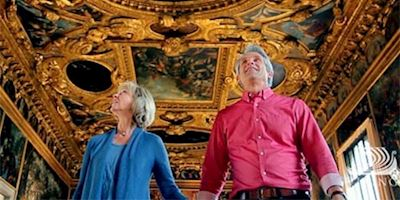 A couple holding hands, looking at a gold gilded and intricately painted ceiling.