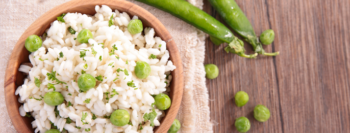 Risi e Bisi - White rice in a brown bowl with green peas sprinkled on top and to the side.