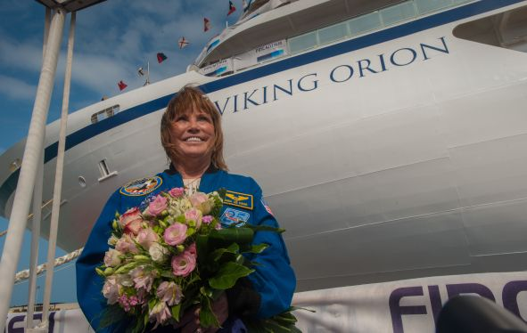A woman standing with a boquet of flowers in front of the Viking Orion Ocean Ship.