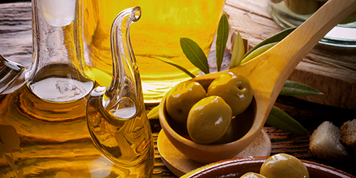 Traditional Olive Oil from Croatia in a dispenser, a spoon with three olives, and olive leaves.