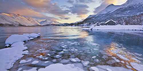 Ice and snow floating in dark water with a sunset and snowy mountains.