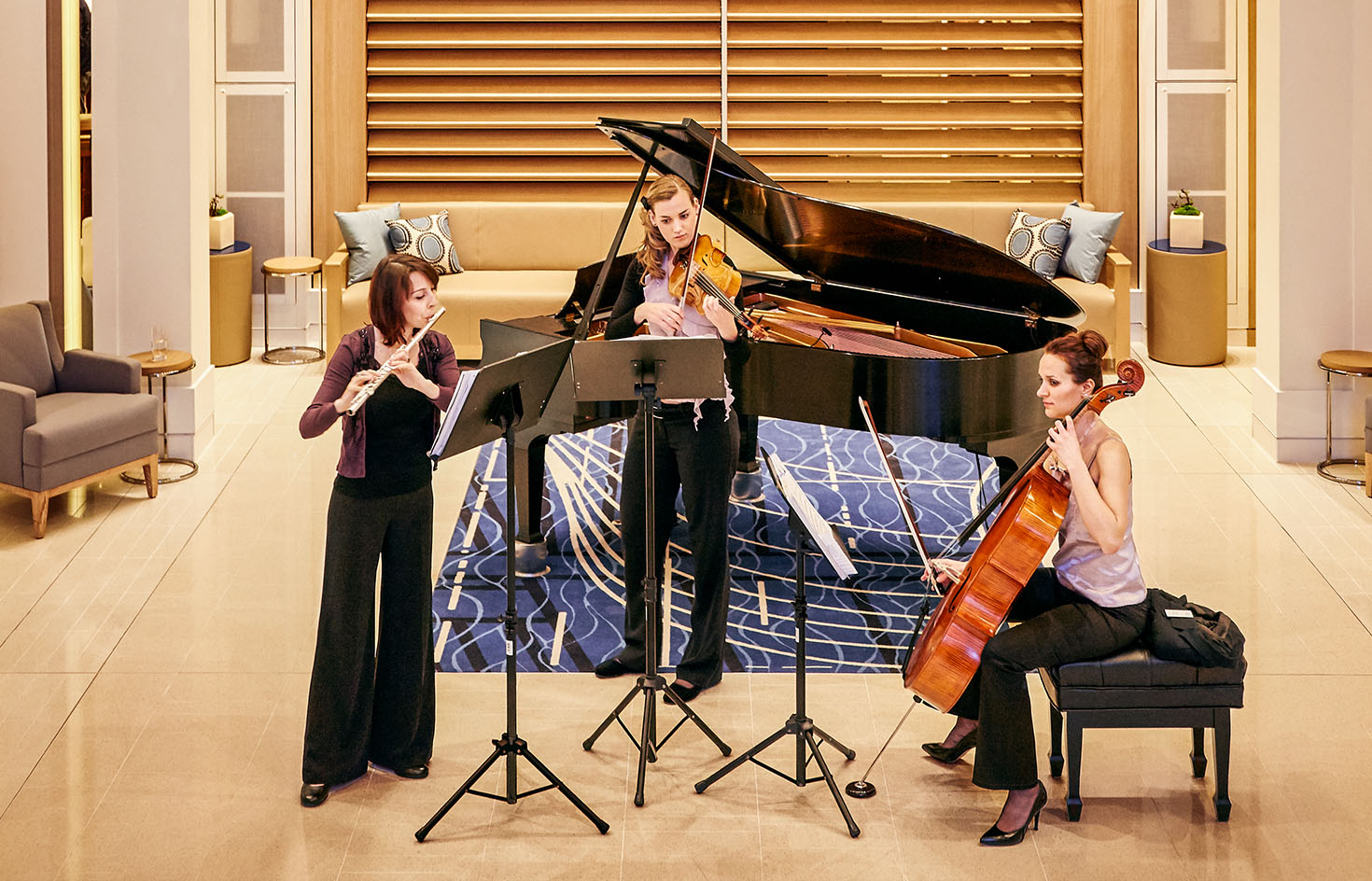 Three women performing music in front of a piano