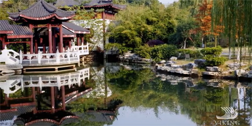 Chinese gardens and buildings over a small, tranquil pond.