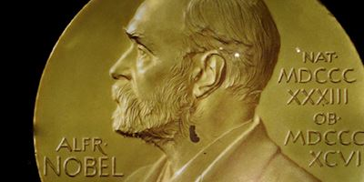 A cropped image of gold embossed with Alfred Nobel's profile and name.